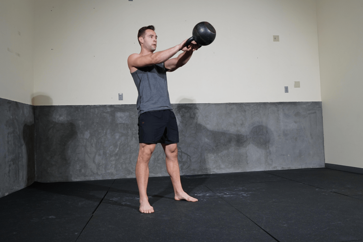 Man with kettlebell in air