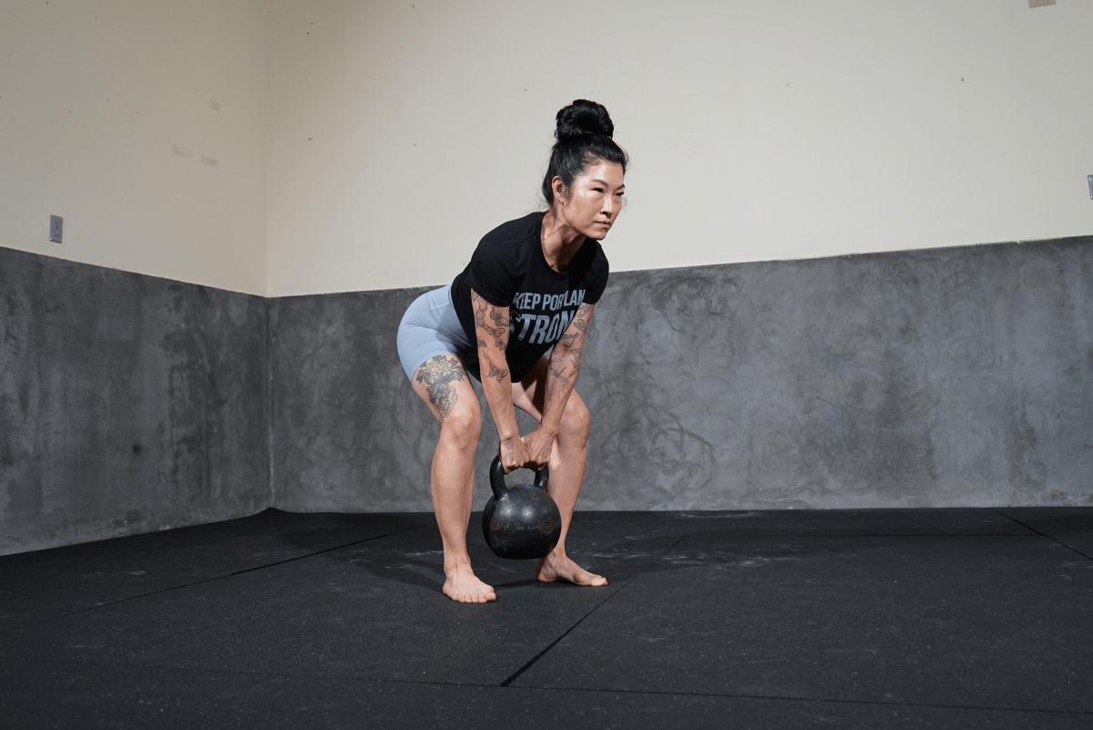 Woman squatting with kettlebell