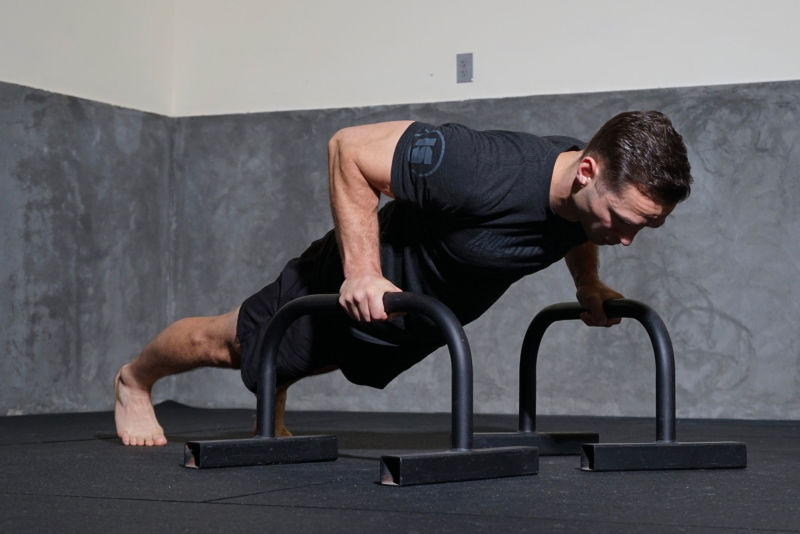 Man doing push-ups with bars on floor