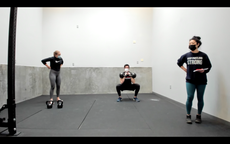 coach squatting with kettlebells
