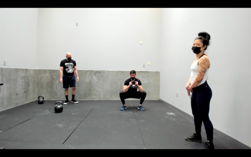 man squatting with kettlebell