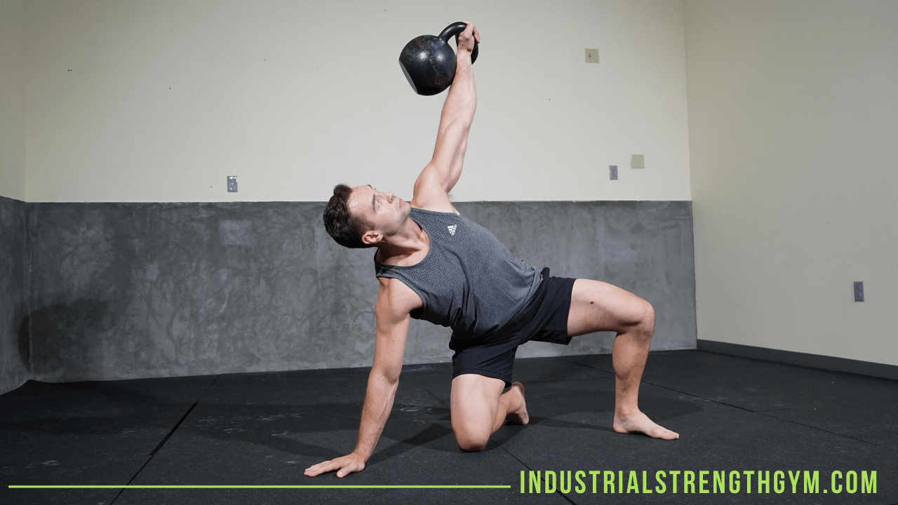 Man doing a turkish get up with a kettlebell