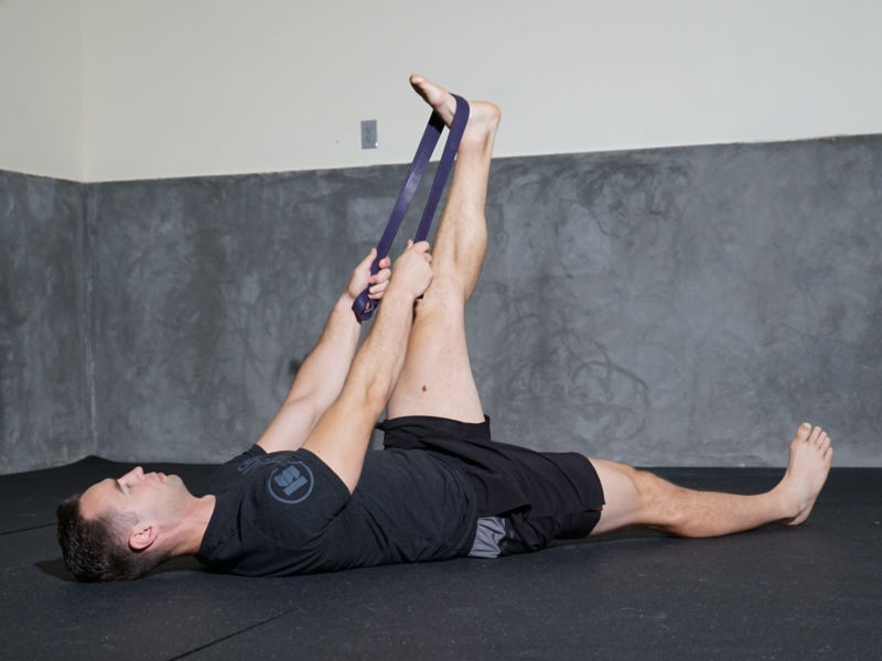 Man stretching hamstring with resistance band